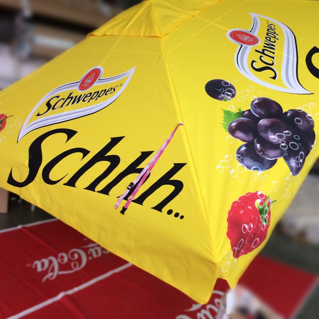 schweppes branded yellow parasol