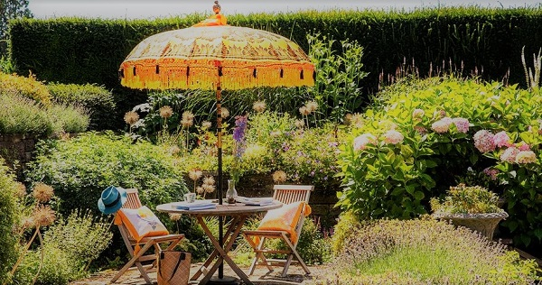 amazing yellow orange decorative parasol in a garden with table