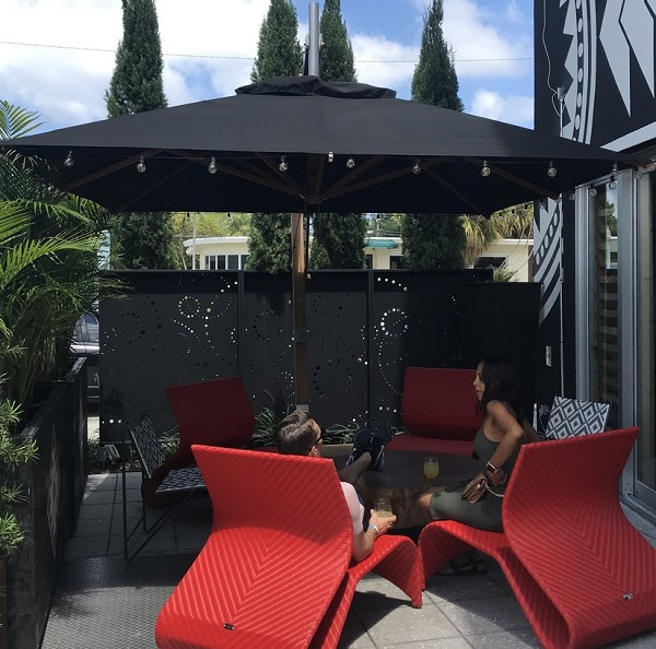 black parasol over table and red long chairs