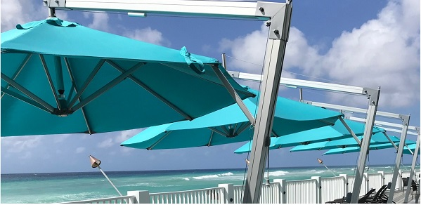 blue cantilever parasols by the sea side