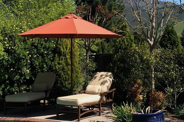home garden parasol with sunchair on the side of the pool