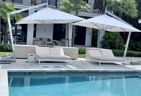 2 mirrored cantilever parasols over sunchairs on the side of the pool
