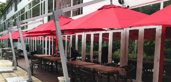 red cantilever parasols shading a terrace with tables