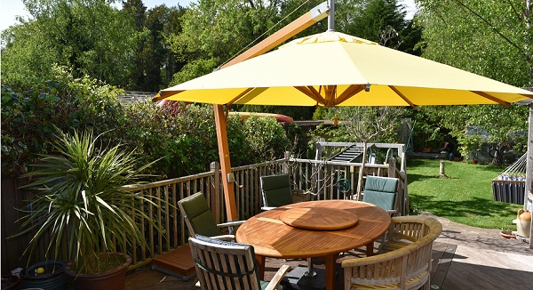 yellow garden parasol with oval table on a patio